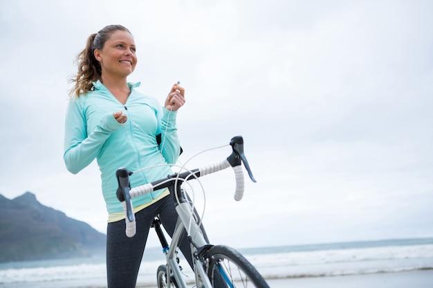Donna felice che sta con la bicicletta sulla spiaggia