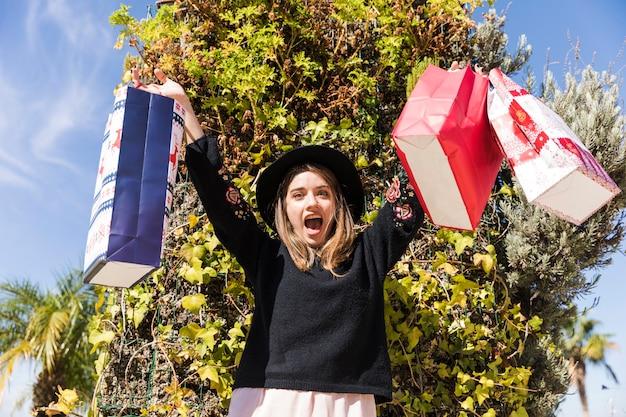 Donna felice che sta sulla via con i sacchetti della spesa