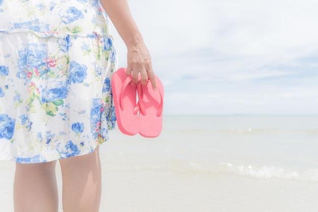 Donna felice che tiene flip-flop rosa sulla spiaggia sabbiosa per il concetto di vacanza estiva.