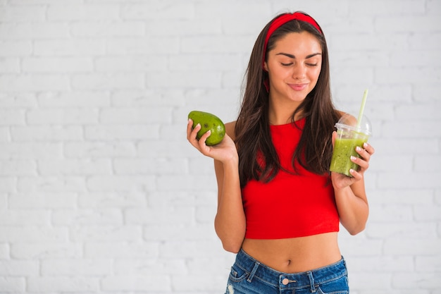 Donna felice che tiene frullati di avocado in tazza di plastica