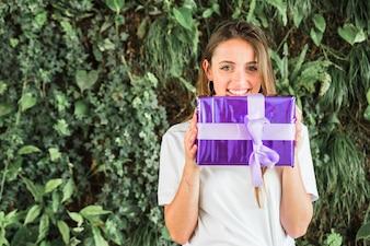 Donna felice che tiene il contenitore di regalo viola