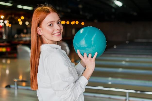 Donna felice che tiene la palla da bowling