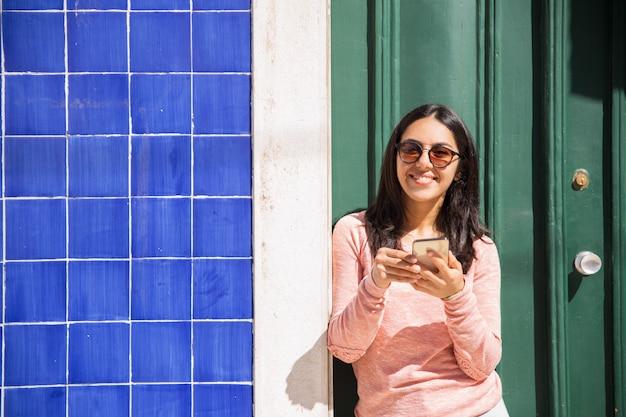 Donna felice che usando smartphone all'aperto