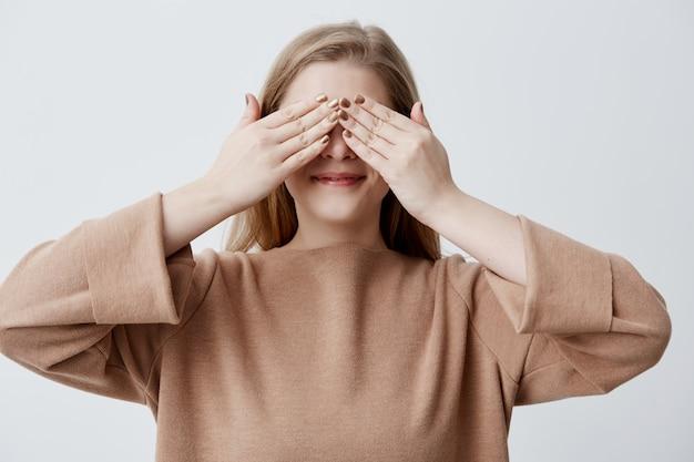 Donna felice chiudendo gli occhi con le mani per vedere sorpresa preparata dal suo ragazzo in piedi, sorridente, in attesa di un regalo. ragazza bionda che copre il viso con le mani