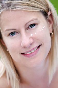 Donna felice con crema sul viso
