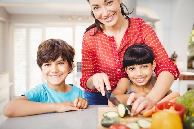 Donna felice con i bambini che tagliano le verdure a pezzi a casa