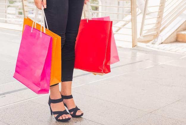 Donna felice con i sacchetti della spesa che gode nello shopping. donne che acquistano, concetto di stile di vita