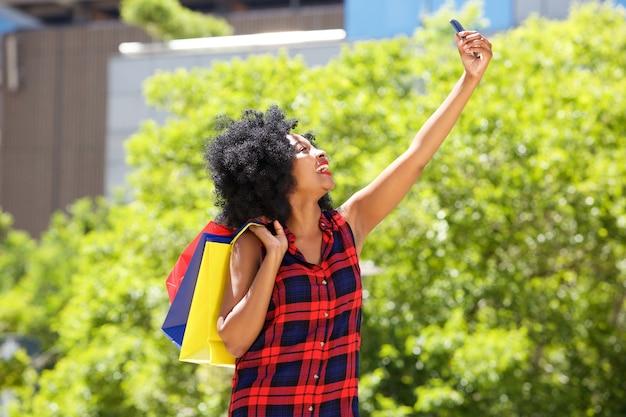 Donna felice con i sacchetti della spesa che prendono selfie fuori