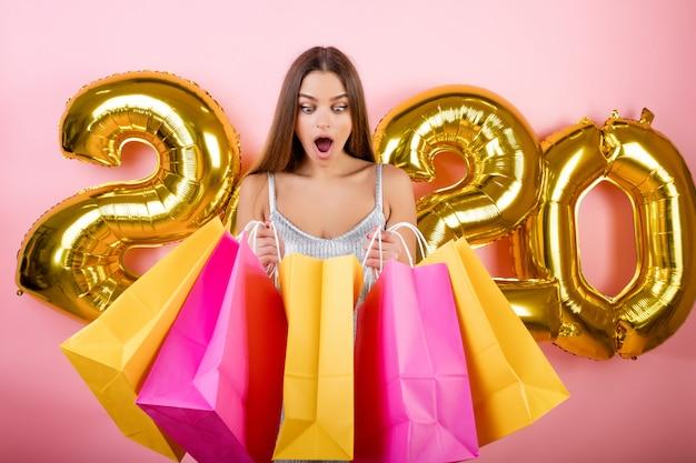 Donna felice con i sacchetti della spesa variopinti con i palloni di natale 2020 isolati sopra il rosa