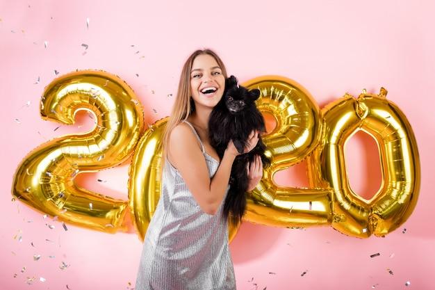 Donna felice con il cane nero dello spitz giapponese e coriandoli e palloni dorati del nuovo anno 2020 isolati sopra il rosa