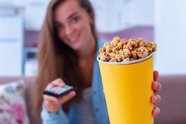 Donna felice con il contenitore di popcorn al caramello croccante durante la visione di film a casa