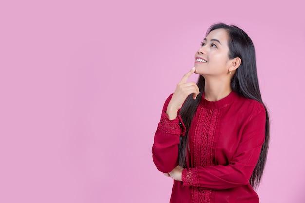 Donna felice con il dito indice sul mento
