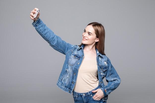 Donna felice con il sorriso raggiante che fa selfie isolato sulla parete grigia