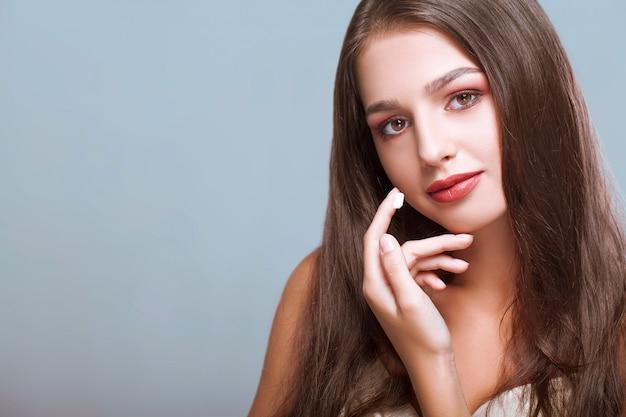 Donna felice con il viso sano, applicare la crema sotto gli occhi