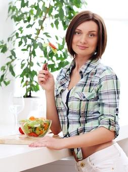 Donna felice con la ciotola di insalata fresca