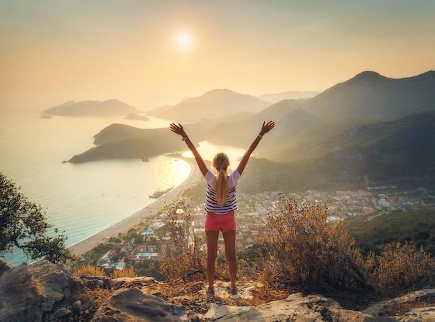Donna felice con le braccia alzate in piedi sulla montagna