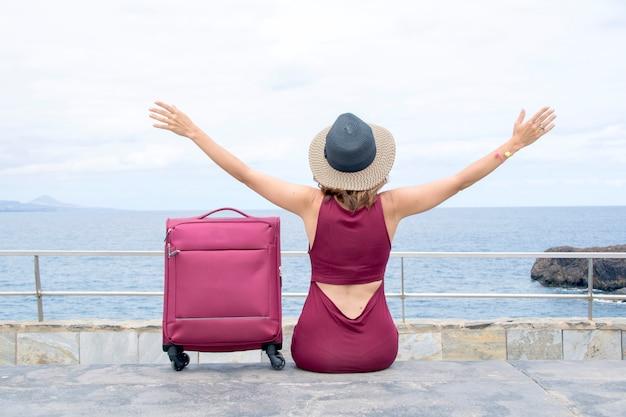 Donna felice, con le braccia alzate, seduta di fronte al mare, con la sua valigia da viaggio al suo fianco.