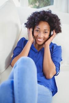 Donna felice con le cuffie sul divano