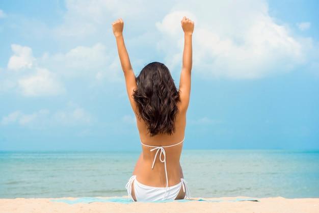 Donna felice con le mani nell'aria che si distende alla spiaggia in estate
