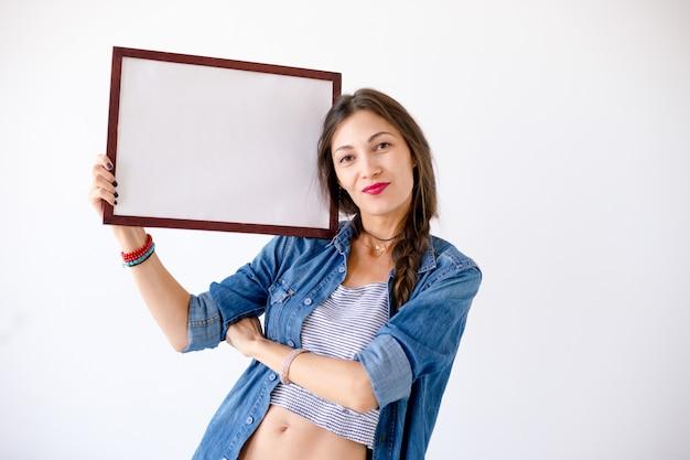 Donna felice con un cartello o un manifesto bianco in bianco