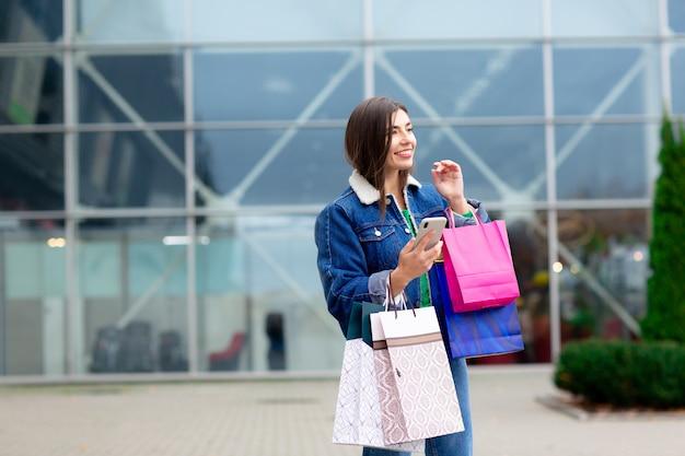Donna felice del brunette con i sacchetti della spesa che gode nell'acquisto e nel fare i selfie. comperando, concetto di stile di vita