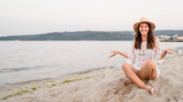 Donna felice del colpo completo che si siede sulla riva