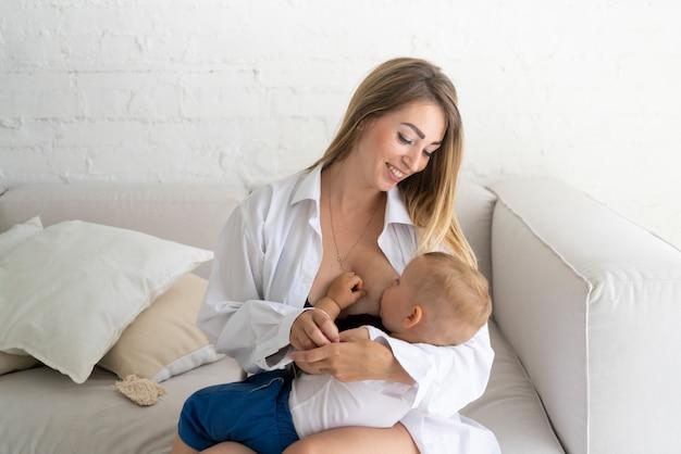 Donna felice del colpo medio che allatta al seno il suo bambino