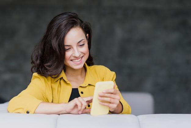 Donna felice del colpo medio che esamina telefono
