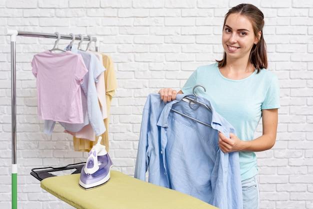 Donna felice del colpo medio che mette chemise sul gancio