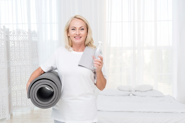 Donna felice del colpo medio con la stuoia di yoga e dell'acqua