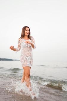 Donna felice del colpo pieno che posa in mare