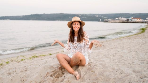 Donna felice del colpo pieno che si siede sulla sabbia