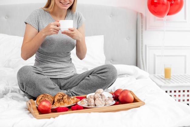 Donna felice del primo piano che mangia prima colazione
