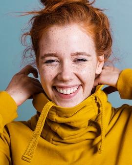 Donna felice del primo piano con la maglia con cappuccio gialla e il fondo grigio