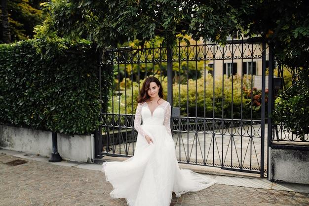 Donna felice della sposa in una posa del vestito da sposa