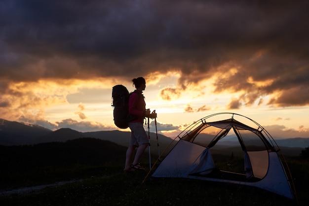 Donna felice della viandante che sta vicino alla tenda con lo zaino sulle sue spalle