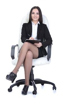 Donna felice di affari che si siede su una sedia.