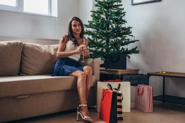Donna felice di festa di natale con i sacchetti della spesa a casa. nuovo anno