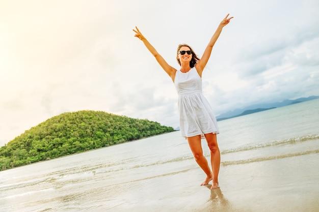 Donna felice di libertà con le braccia alzate sulla spiaggia al giorno pieno di sole
