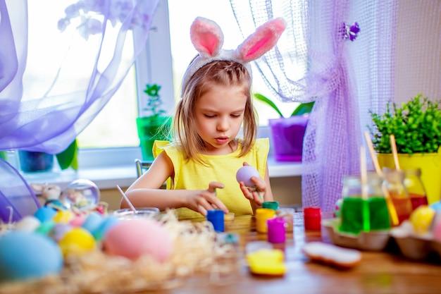 Donna felice di pasqua in orecchie del coniglietto che dipingono le uova, piccolo bambino a casa. vacanze di primavera