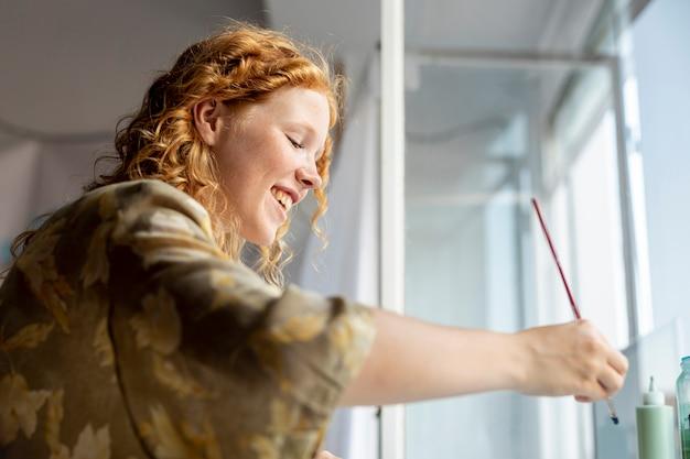 Donna felice di vista laterale che tiene una spazzola