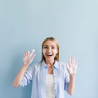 Donna felice divertirsi mentre si lava le mani e il viso