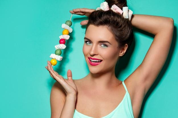 Donna felice e bella con caramelle dolci allo spiedo
