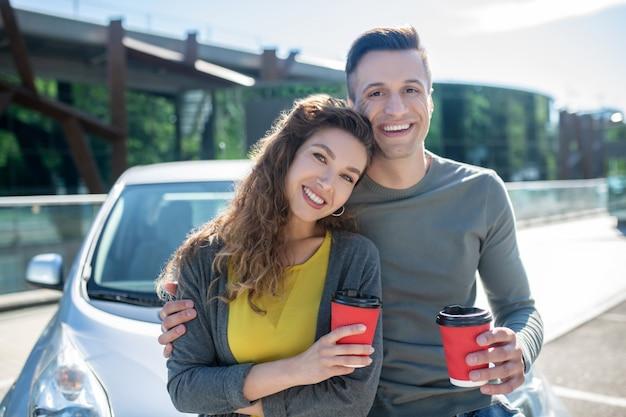 Donna felice e uomo che la abbraccia in piedi con il caffè