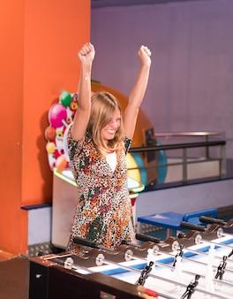 Donna felice giocando a biliardino