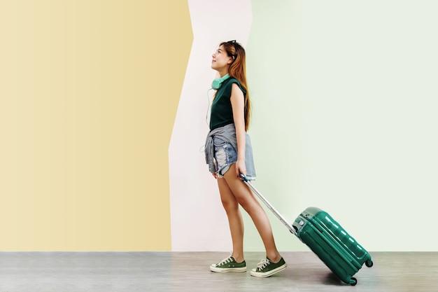 Donna felice giovane viaggiatore camminando con valigia e musica cuffie