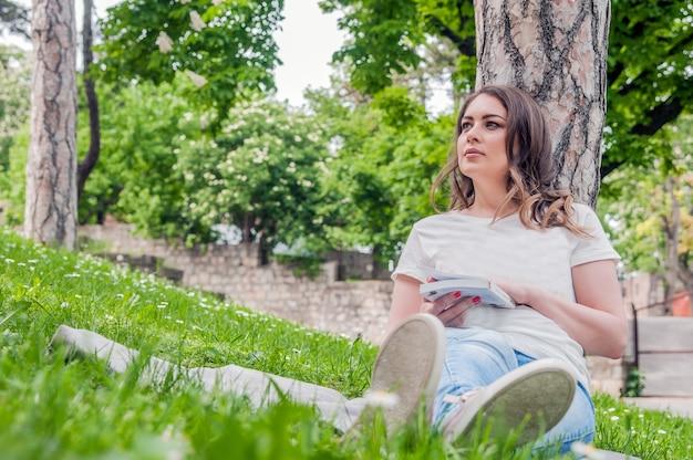 Donna felice godendo la vita in campo con fiori. bellezza della natura, cielo nuvoloso blu e campo colorato con fiori. stile di vita all'aperto. concetto di libertà. donna nel campo estivo