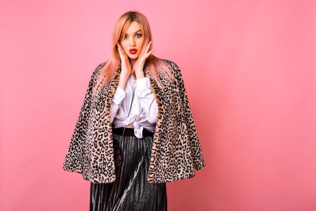 Donna felice hipster ballando e divertendosi al fondo rosa dello studio, indossando l'abito da cocktail party e il cappotto di leopardo di pelliccia, tempo di vacanze invernali.