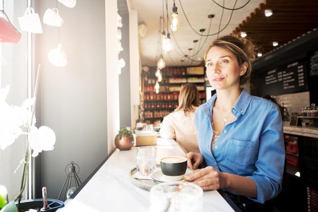 Donna felice in camicia blu in una caffetteria