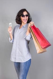 Donna felice in camicia con borse e carta di credito